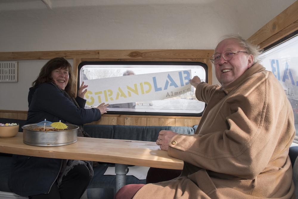 Liesbeth Jansen, directeur van bureau Linkeroever en wethouder Frits Huis leggen de laatste hand aan het aanbrengen van het StrandLAB-logo. Foto Jan Dekker